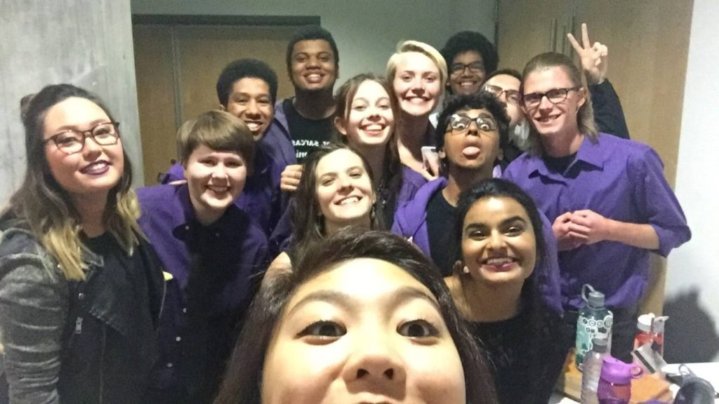 A selfie of a lot of the Hooligans, in purple, smiling and making silly faces.