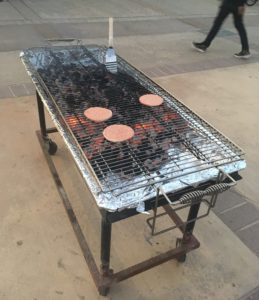 This picture shows that a metal grilling surface has been put over the coals, so that there's something to put the patties on. There are 3 relatively raw patties on the grill.