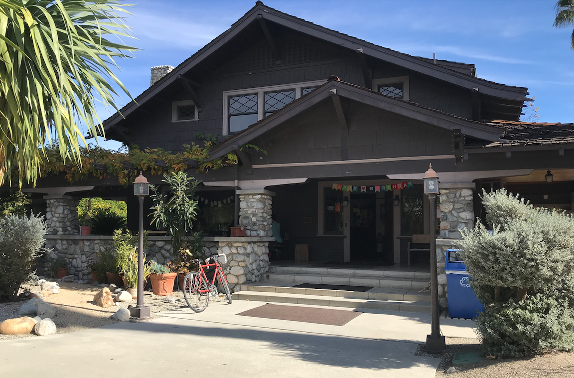 Front of the Grove House at Pitzer; the grove house is an old craftsman style house with a large front porch and seating for eating and doing work