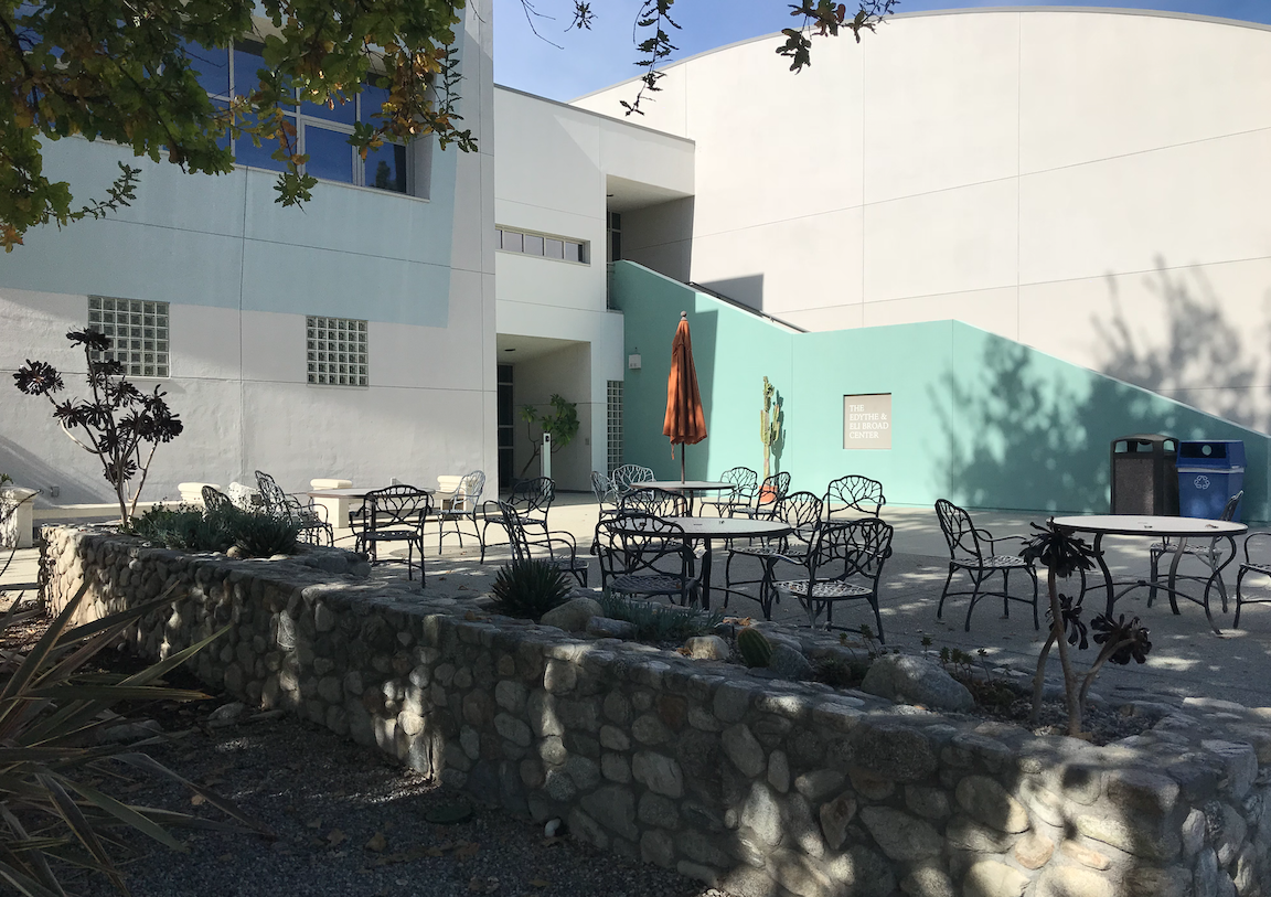 Several tables in the shade next to a building at Pitzer