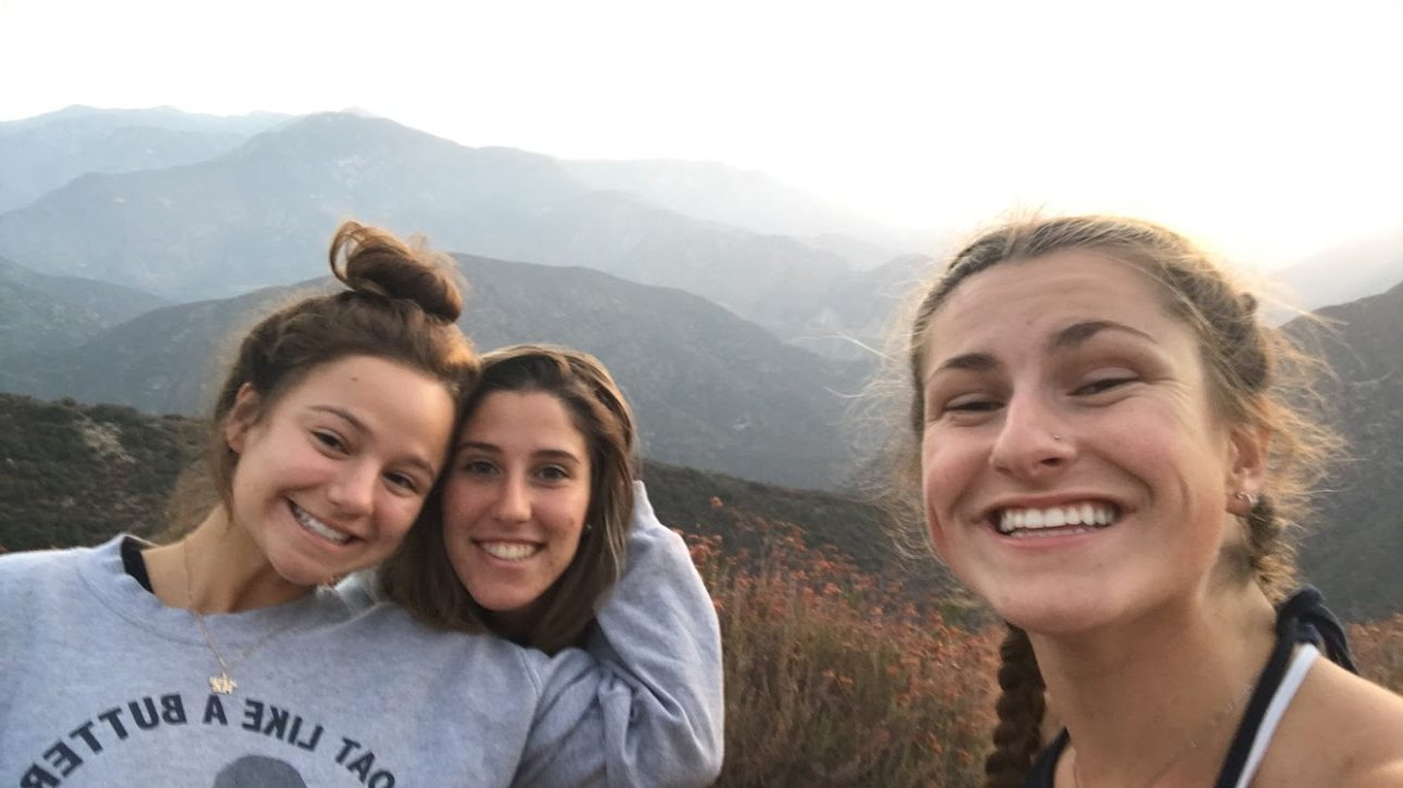 A selfie of three girls smiling in front of a range of mountains.