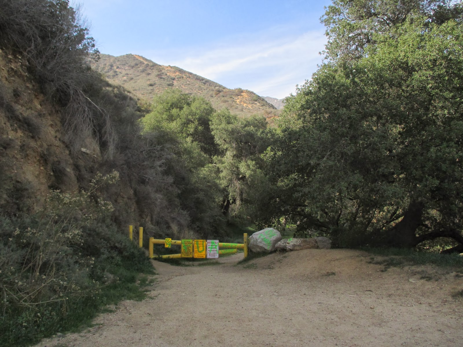 A yellow gate, which marks the start of the trail, is surrounded by trees and bushes