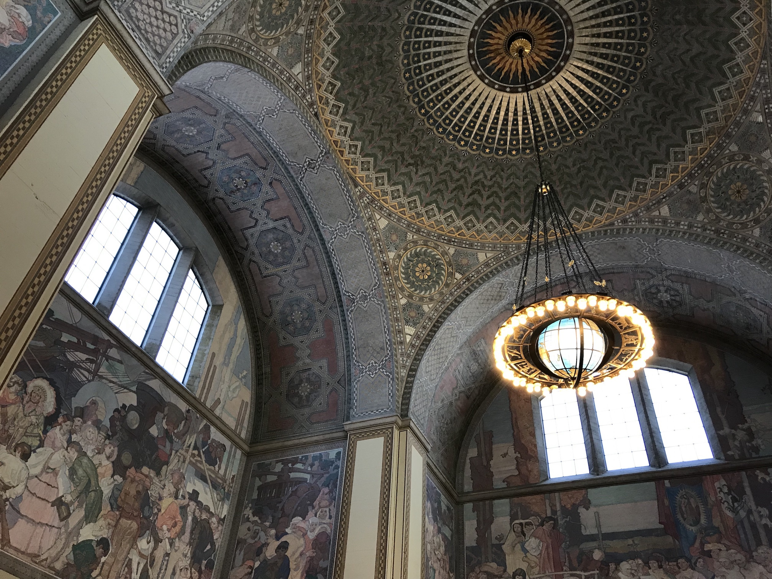 This space has a mosaic tile ceiling and a globe chandelier. Large windows provide lots of natural light