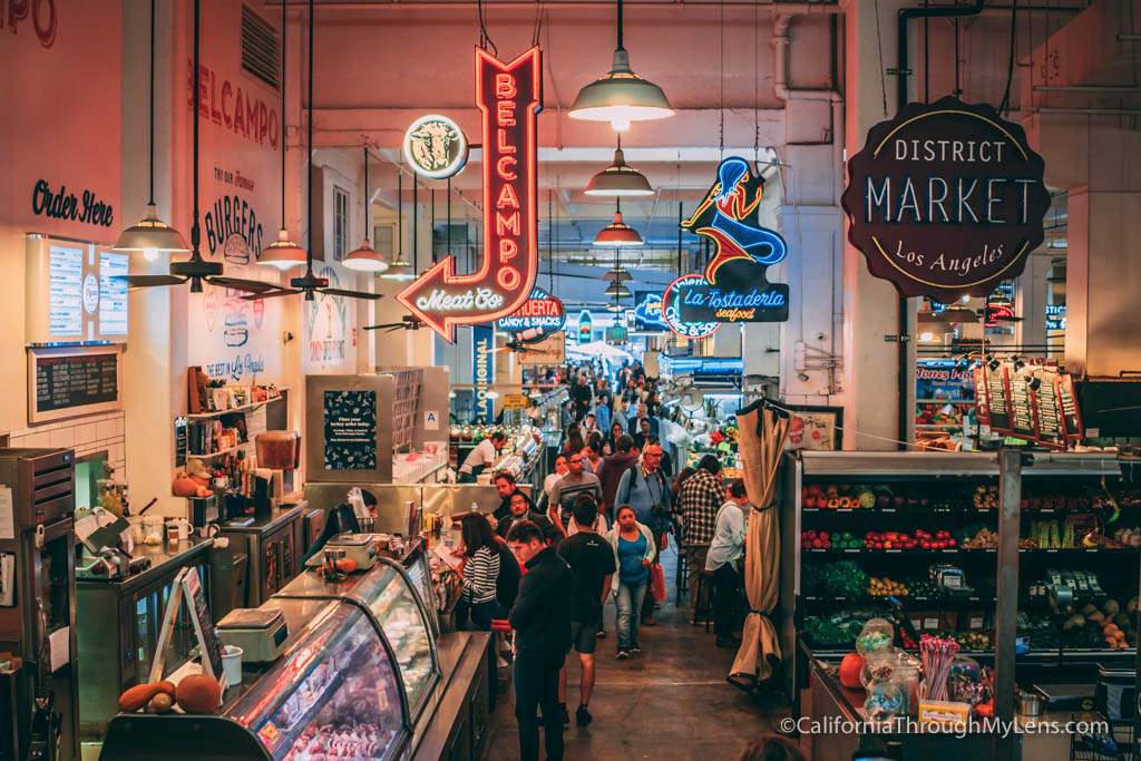 Grand Central Market is packed with people; lots of colorful signs hang from the ceiling for each food booth