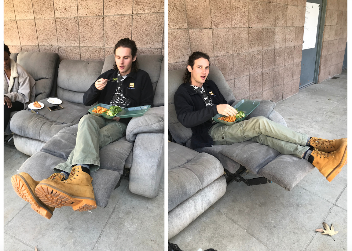 Bradley is wearing a black clinic fleece, green pants, and yellow-brown work boots. He is sitting on a couch and eating out of his green box