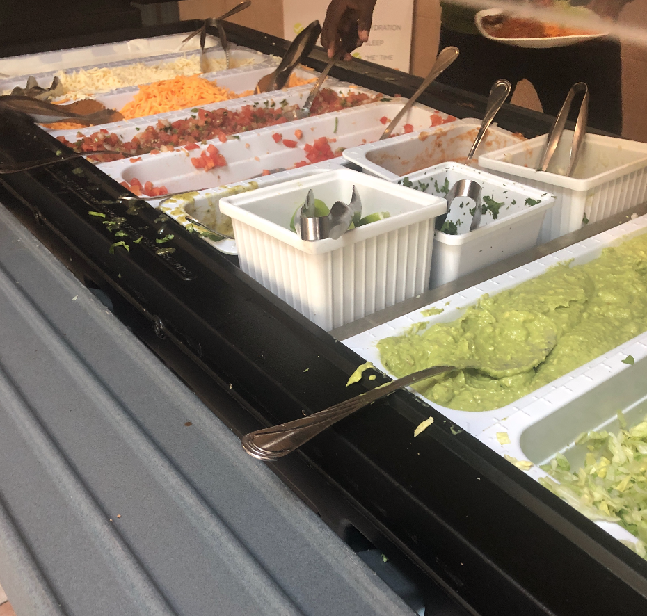 The fajita topping bar has guac, cheese, tomatoes, lettuce, cilantro, green onions, and pico de gallo