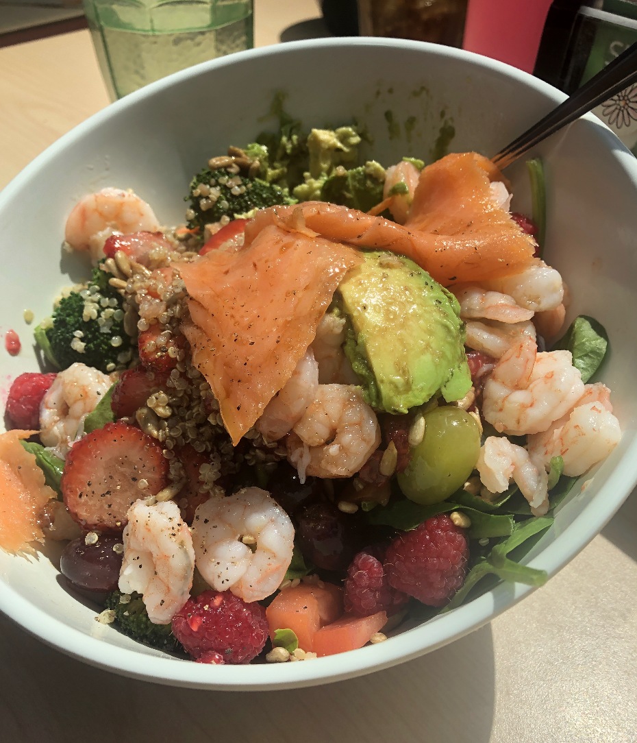 A pre-shaken salad with shrimp, smoked salmon, berries, avocado, quinoa, grapes, and tomato