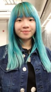 The picture is a selfie of Shanni. She is wearing a jean jacket, and has blue, dyed hair.