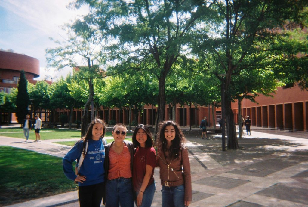 four girls in front of a lawn, trees, and a brown building