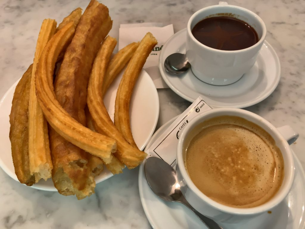 churros, a cup of hot chocolate, and a cup of coffee