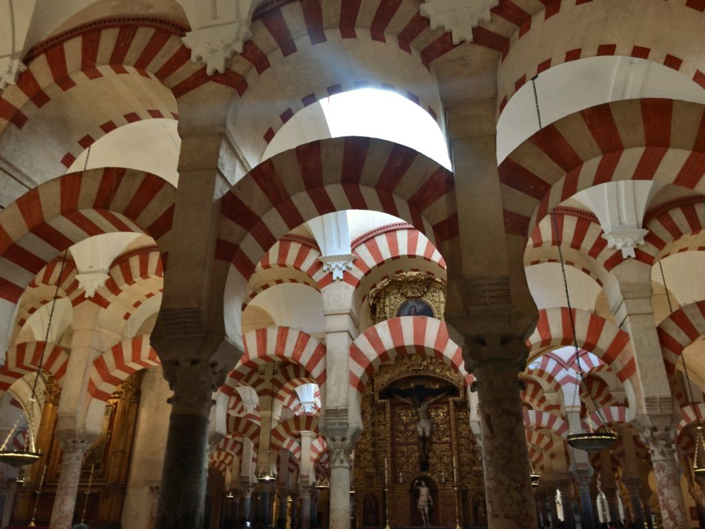 Red-and-white alternating double arches and columns inside a Spanish mosque