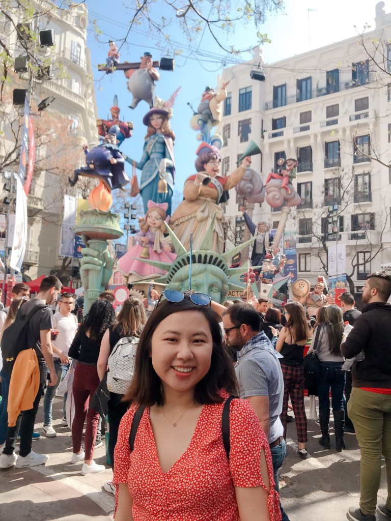 Jasmine and a crowd in front of a large, colorful monument of the Statue of Liberty and other American symbols