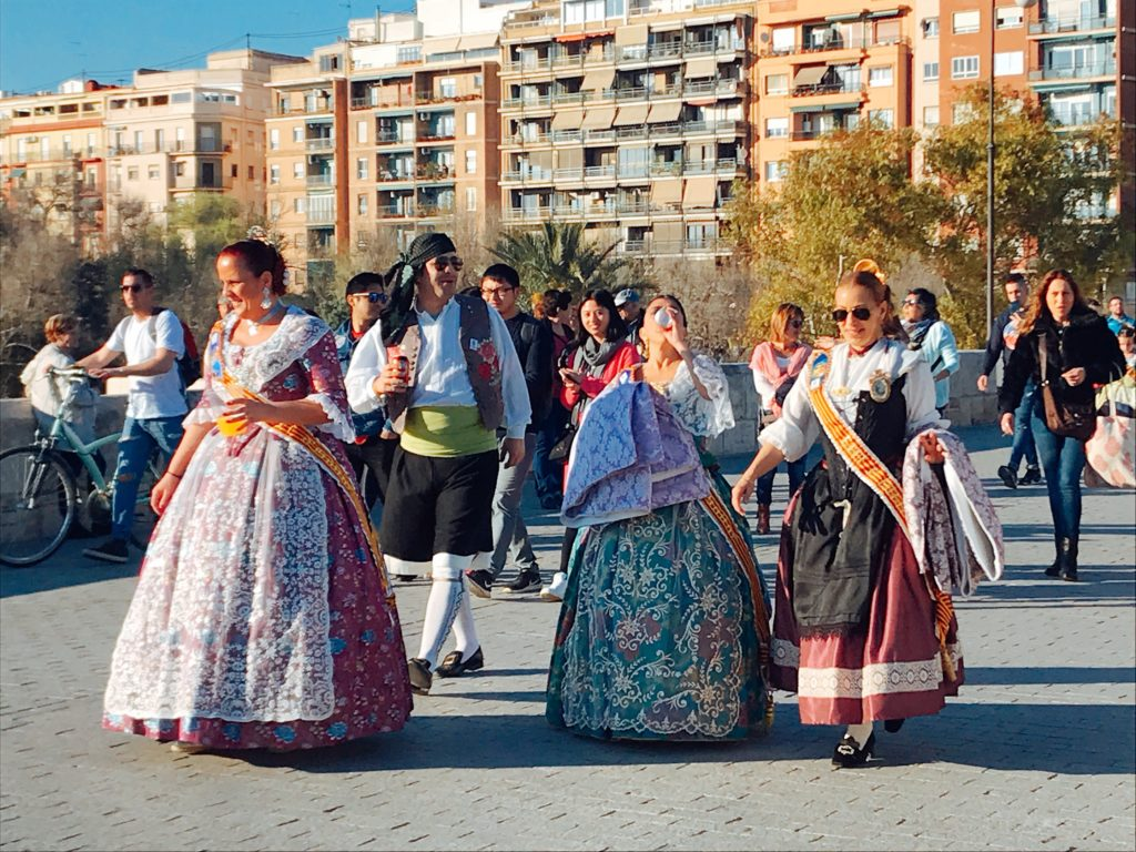 women and men in Spanish costumes walking