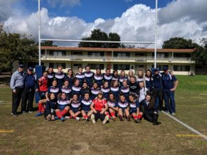 Photo of the 2018-2019 Women's Rugby team. There are 32 players and 5 coaches. everyone is wearing a blue uniform except for two player and a coach. The coach is wearing a grey sweater and the two players are wearing red jerseys.