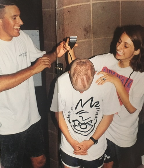 Two students shaving a handprint onto another student's head