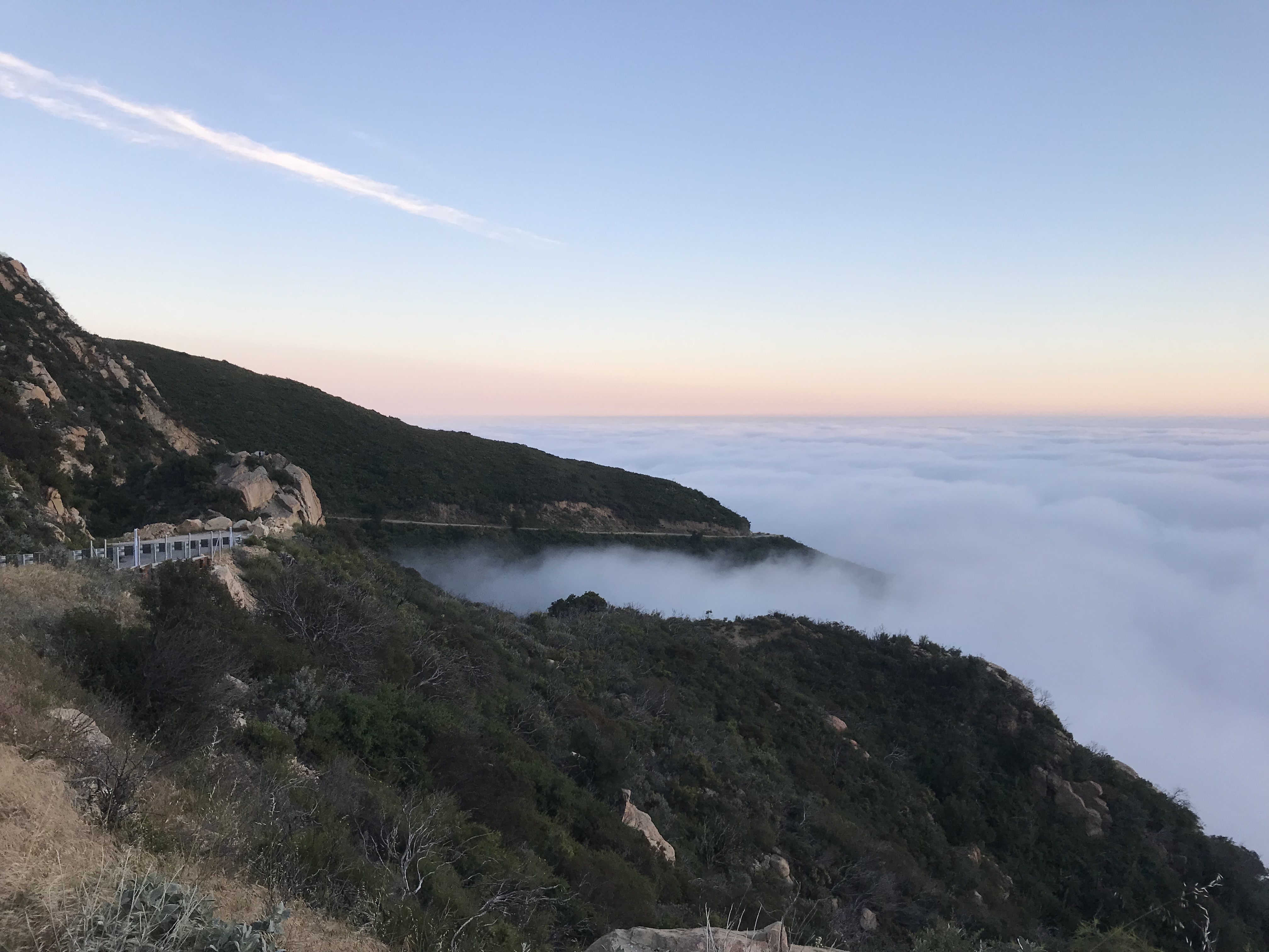 The view from the side of the road near the top of a mountain. The view is above the clouds, which creep into the mountainside. The sky is slightly orange from the sunset.
