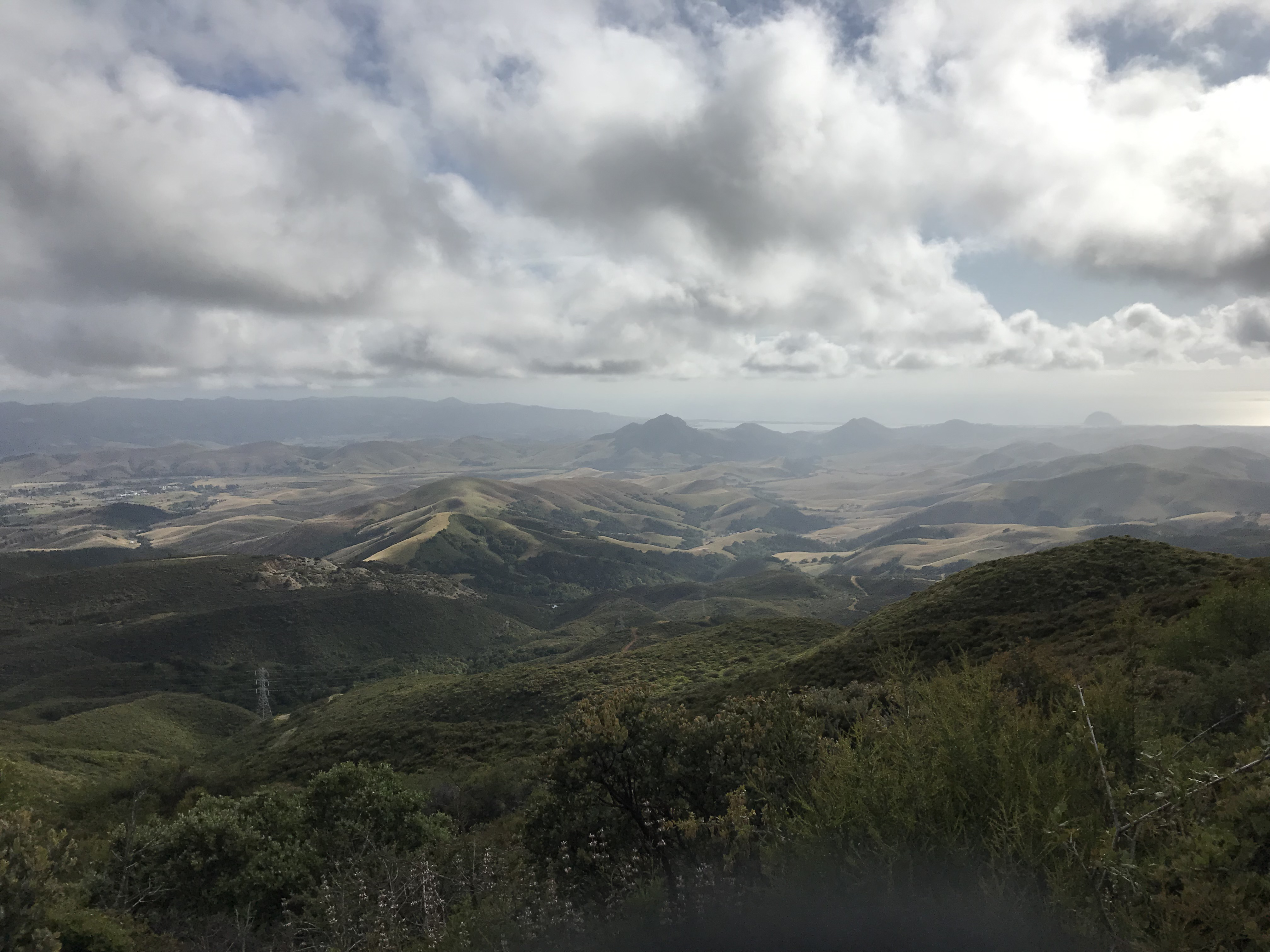 A view during the drive up to Pismo Beach. The clouds are low and there are lots of rolling hills. The landscape is darkened due to the cloudy sky.