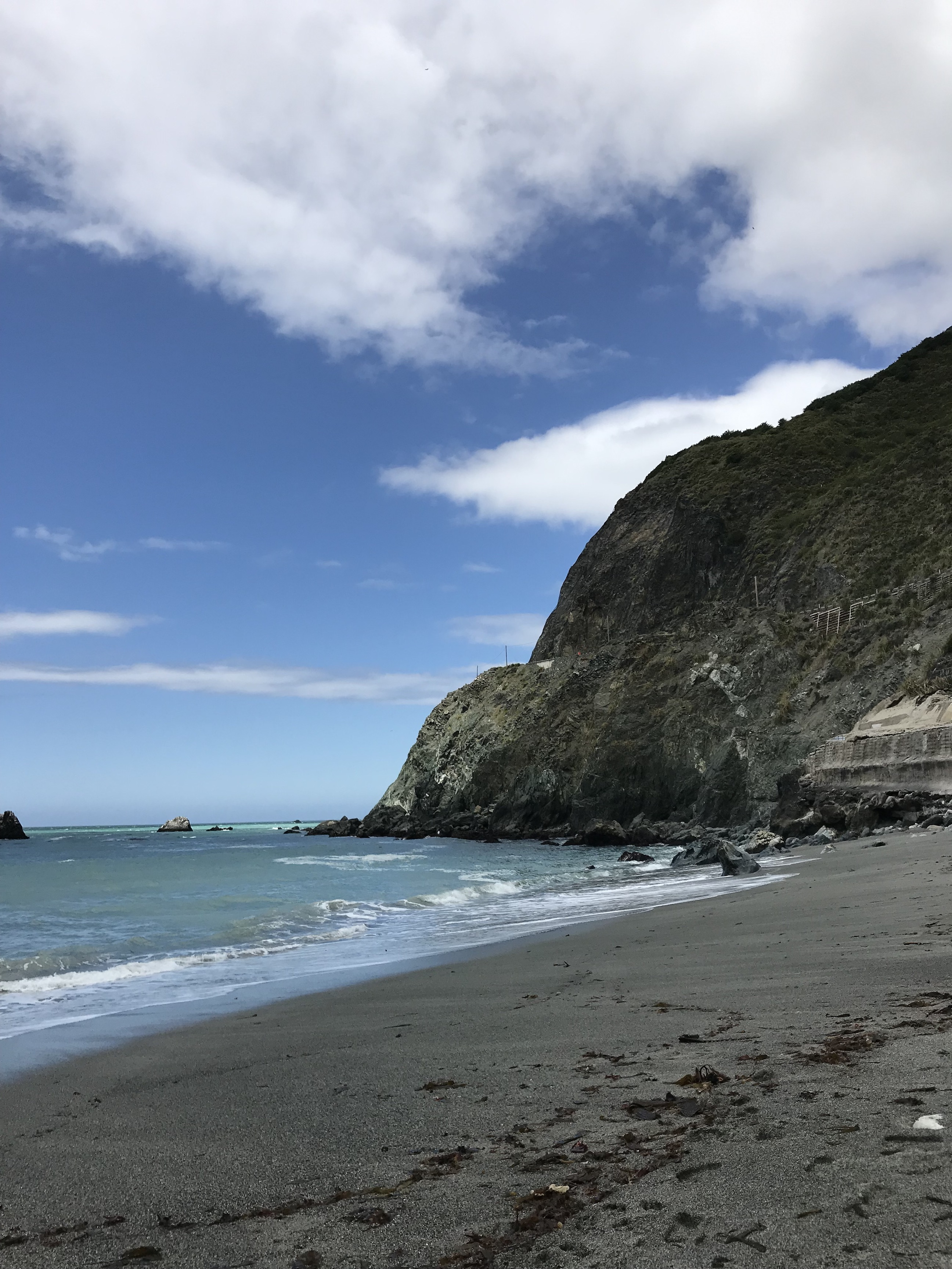The beach at Big Sur. Tall cliffs are on the right side, and the sky is super blue with a couple of white clouds. The sand is a dark color from the pebbles, and the water is pretty calm.