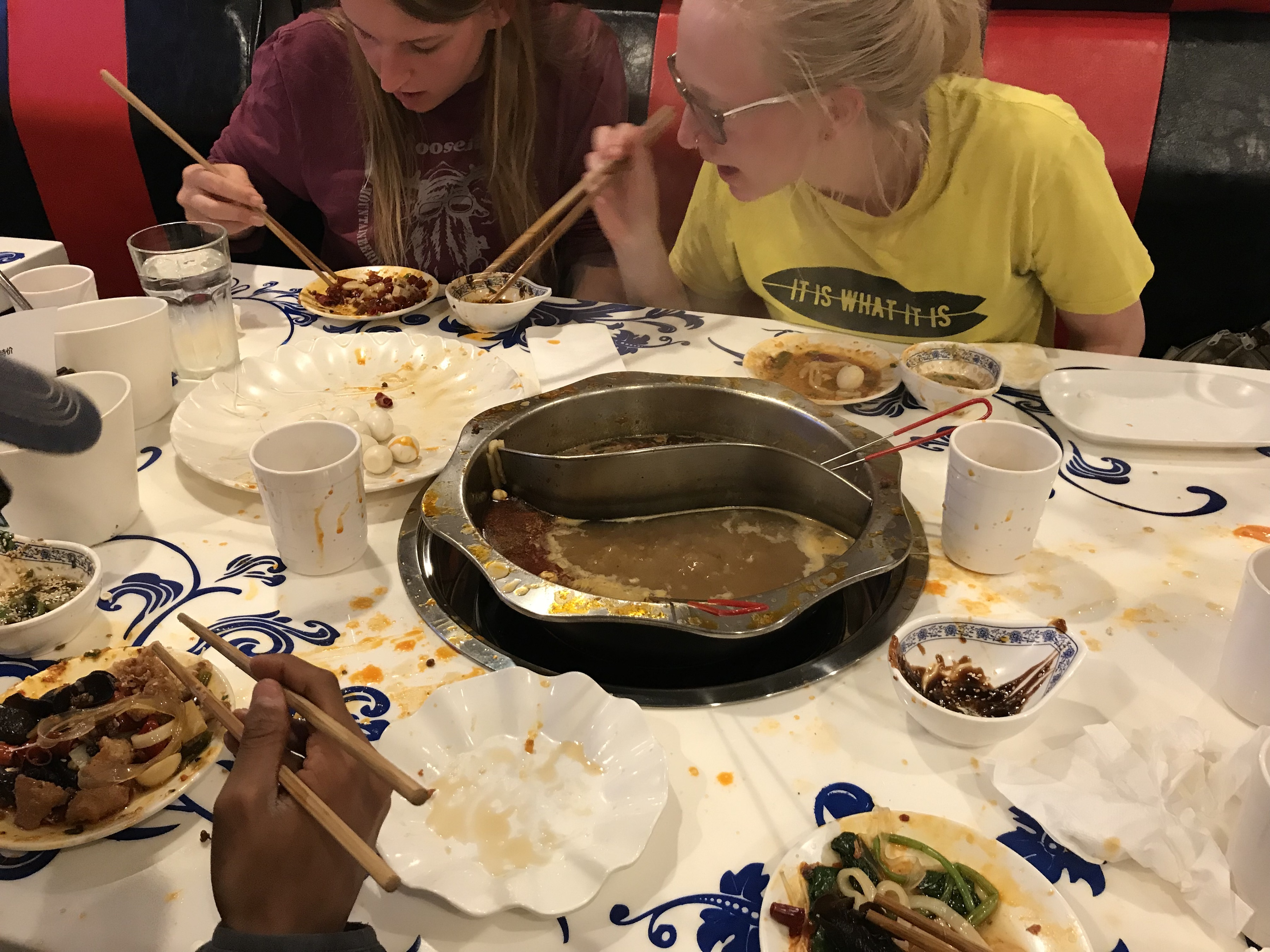 There are several plates on our table at the hot pot restaurant. My friends are picking up their food to eat from the broth.