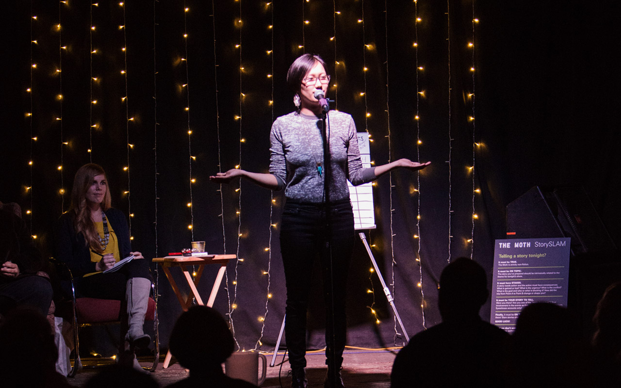 A storyteller stands on stage with her arms stretched out, engaged in her story