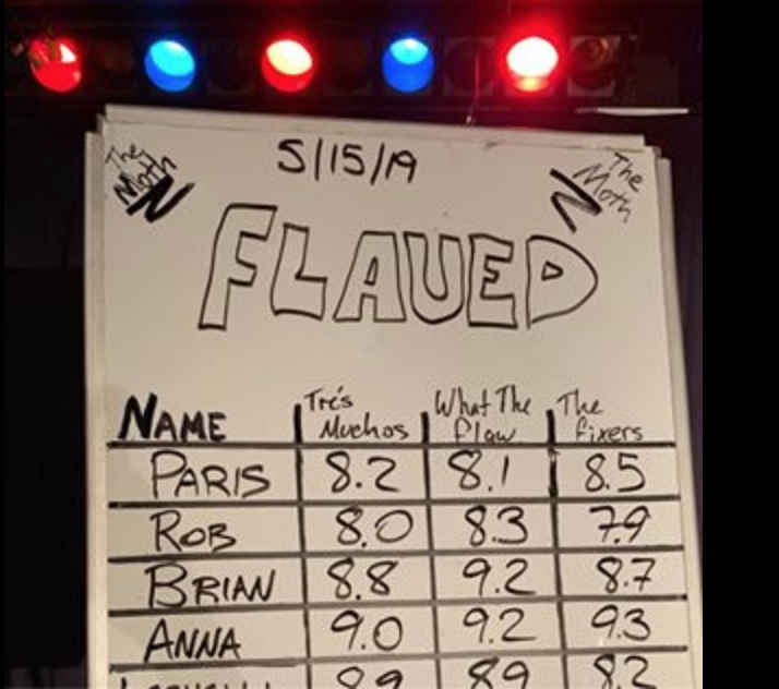 """The scoreboard at a moth story slam event where the theme of the night was """"flawed."""" Names are listed on the whiteboard along with the three scores from the judging teams"""