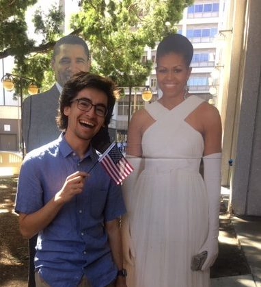 Joaquin posing with an American flag and a cardboard cutout of the Obamas