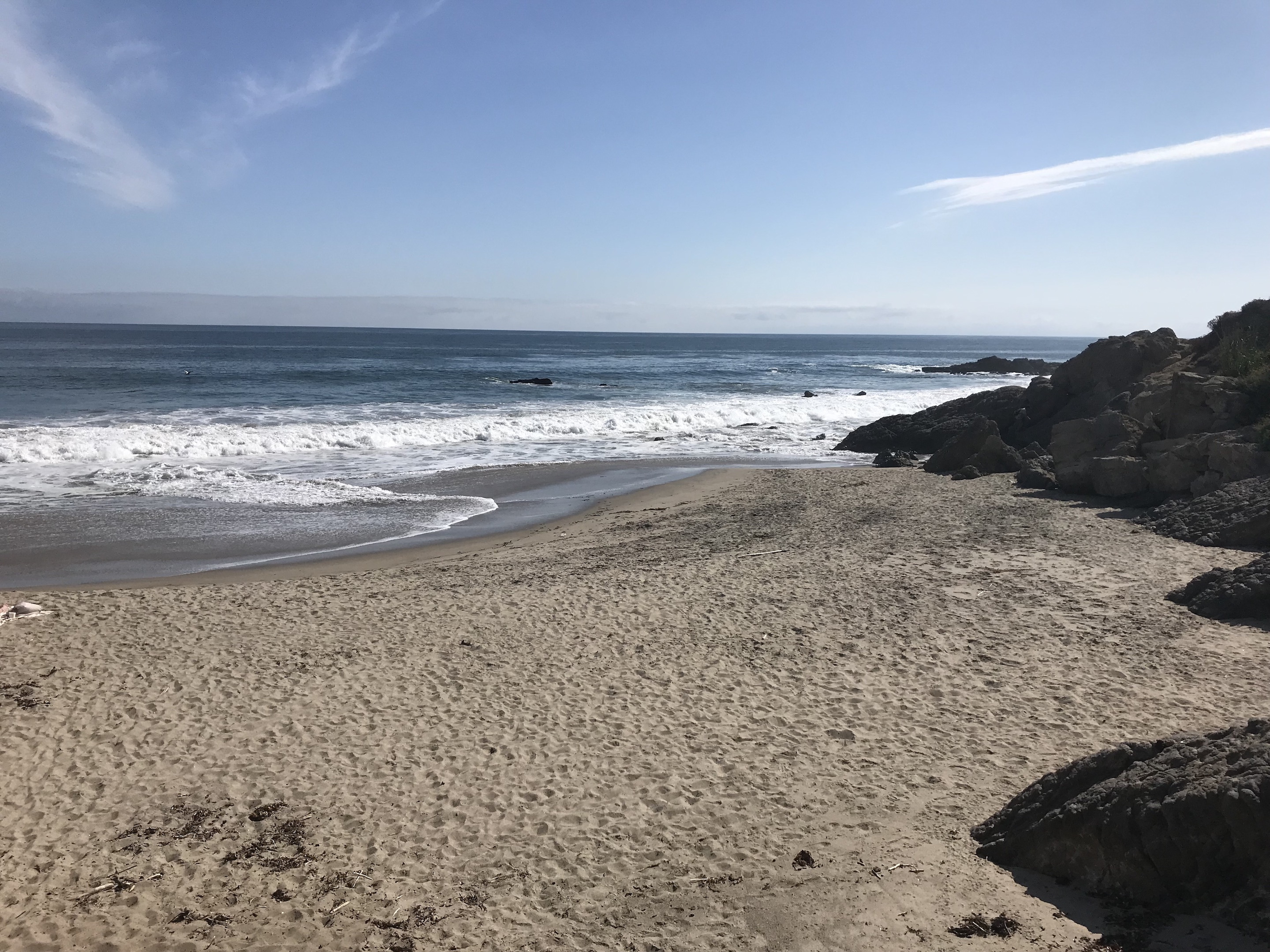 A picture of the cove at Leo Carrillo state park. A sandy beach cove is bordered on the right by rocks, while on the left there is a calm shoreline.