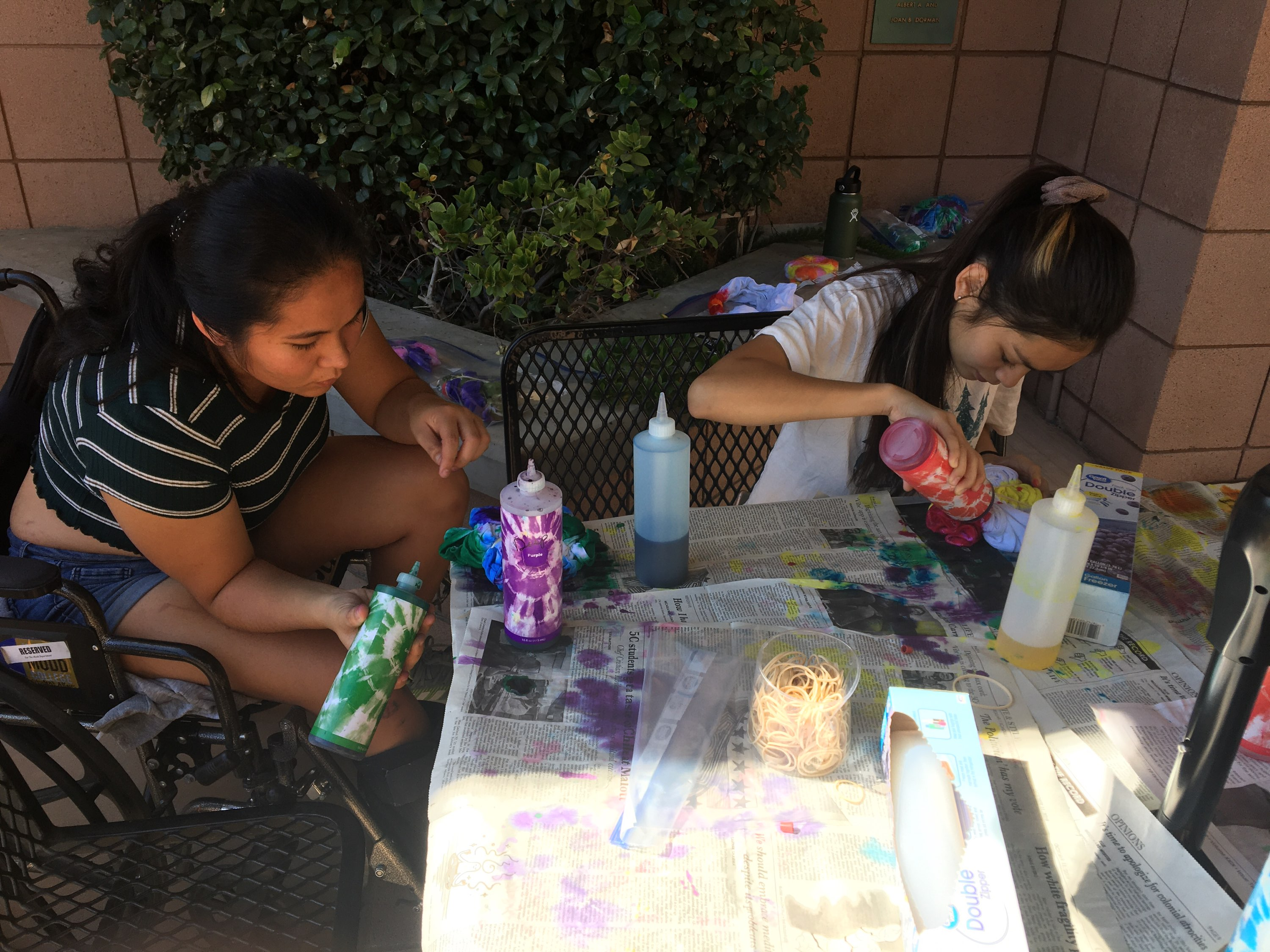 Two Mudd students sitting at a table use bottles of dye on white shirts in front of them.