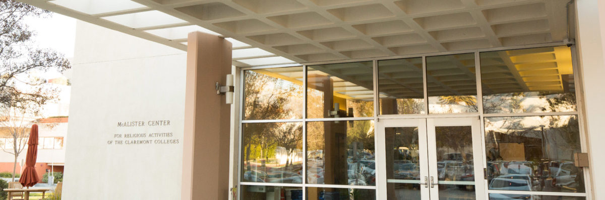 """Glass entrance doors to the McAlister Center with an inscription reading """"McAlister Center: for religious activities of the Claremont Colleges"""" to the side"""