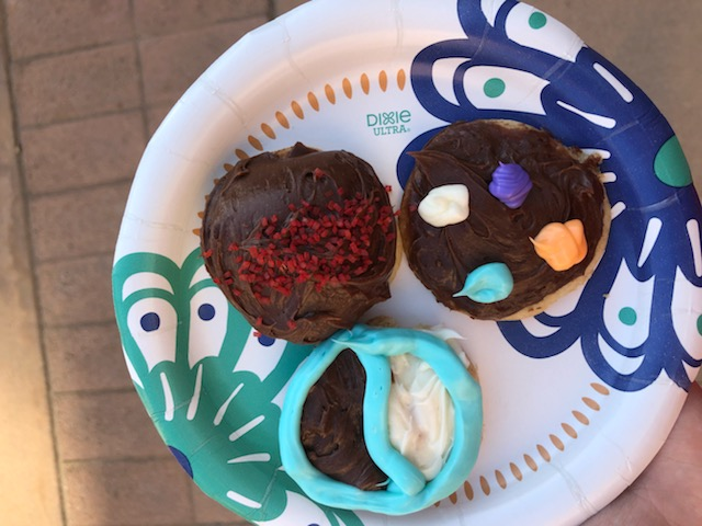 Three cookies, each decorated with brown frosting and colored lines/dots