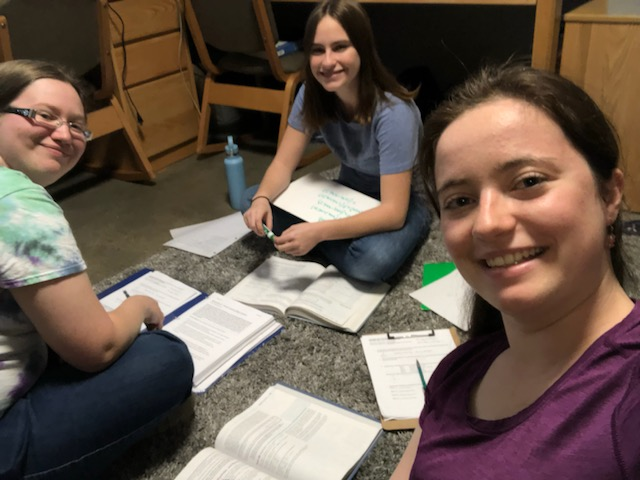 The three of us sitting in a circle on a rug with textbooks and paper