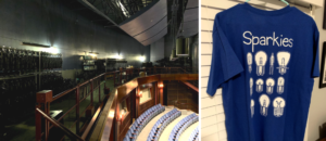 """Left: The left side of the photo displays racks of lights hanging in storage while the right side of the photo is a view of the tops of chairs in the audience of the theatre. Right: Photo shows the back of a blue shirt with the word """"Sparkies"""" at the top and different images of theater light bulbs."""