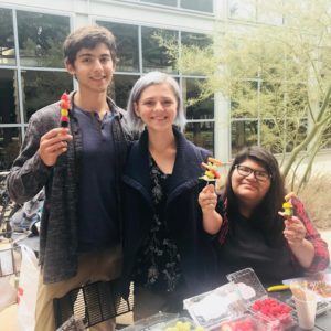A photo of a group of three wellness peers (with me on the right), at the wellness pop-up in front of the Hoch. Everyone is holding a fruit skewer and either sitting or standing in front of a table full of fruit.)