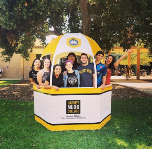 A photo of a group of 8 students inside a white and yellow gazebo with the Office of Health and Wellness along with the Harvey Mudd logo.