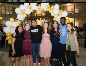 A photo of a group of students dressed nicely with myself near the center left and Dean Michelle on the right, all standing in front of a yellow and white balloon arch.
