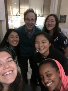 Prof. Dodds, Kailee, and four of her suitemates smile for a selfie outside his office.