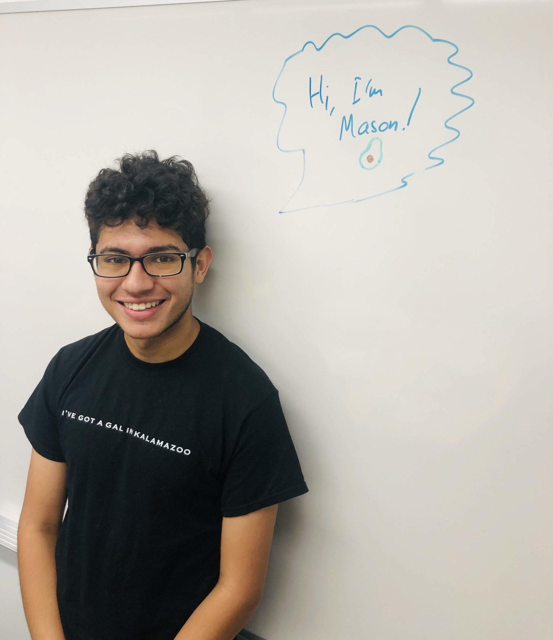 """Intern, Mason Acevedo, leaning up against a whiteboard that reads """"Hi, I am Mason!"""""""