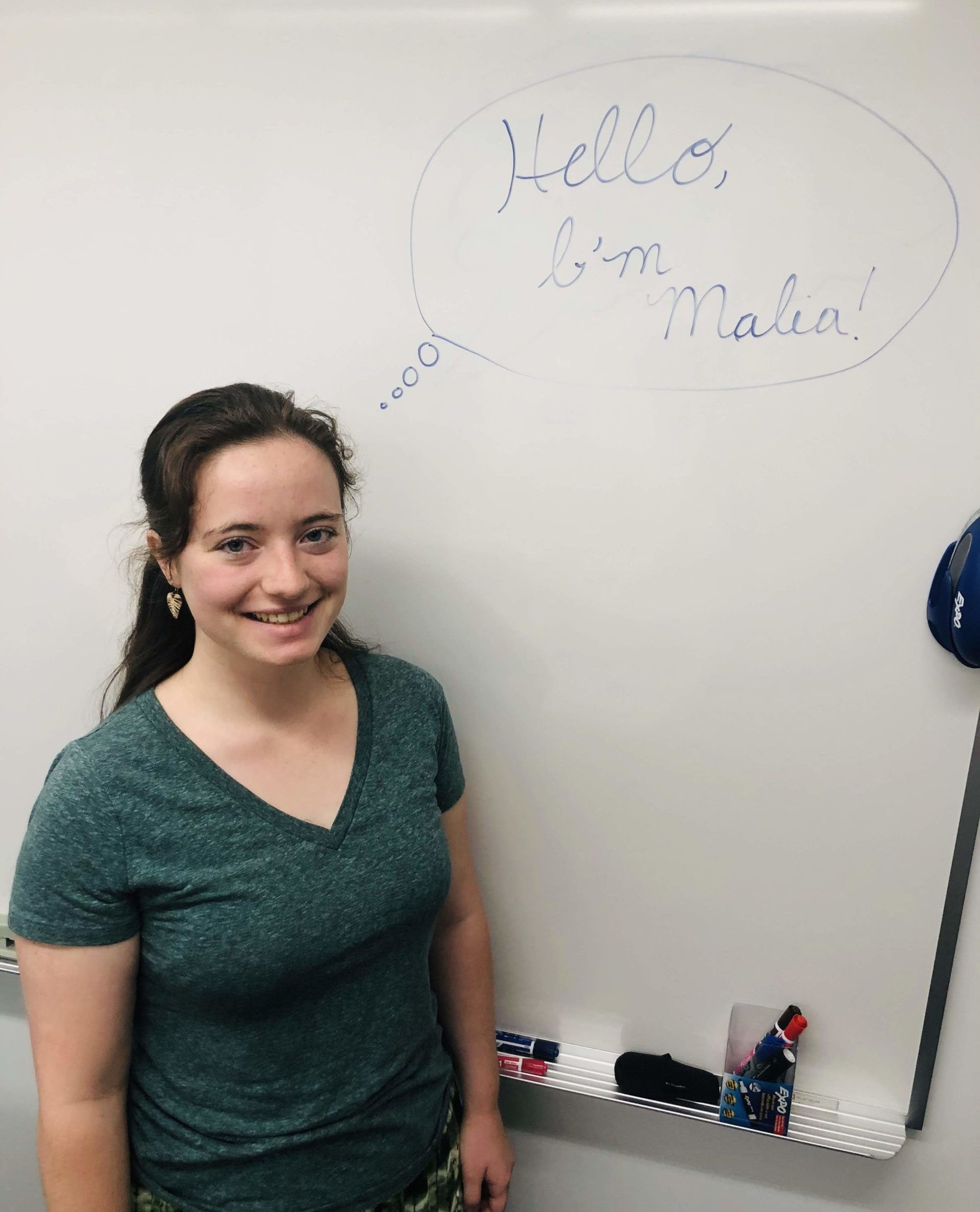 "Intern, Malia Morgan, leaning up against a whiteboard that reads ""Hello, I'm Malia!"""