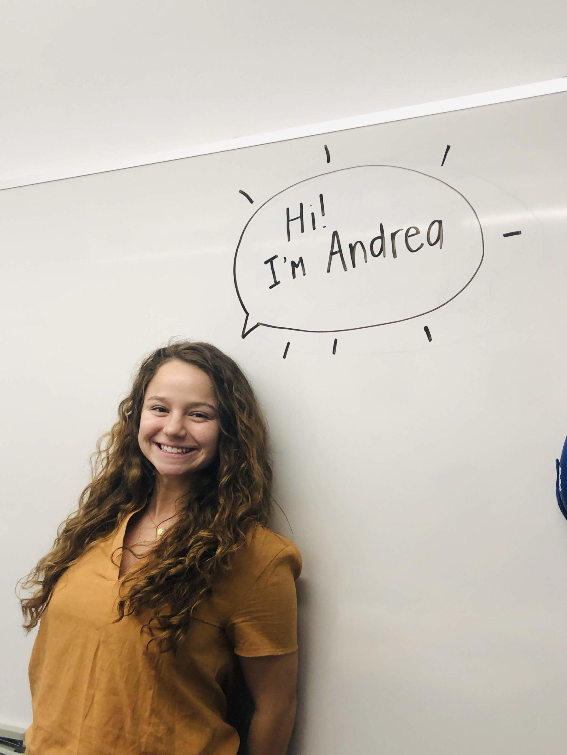 "Intern, Andrea Zavala, leaning up against a whiteboard reading ""Hi! I am Andrea"""