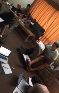 About 6 students in a common room surrounded by laptops and notebooks.