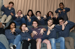 A group of college students sit on two tiers of couches. They are wearing blue sweatshirts (except one person in the middle wearing a purple shirt) and forming M's with their fingers in different ways.