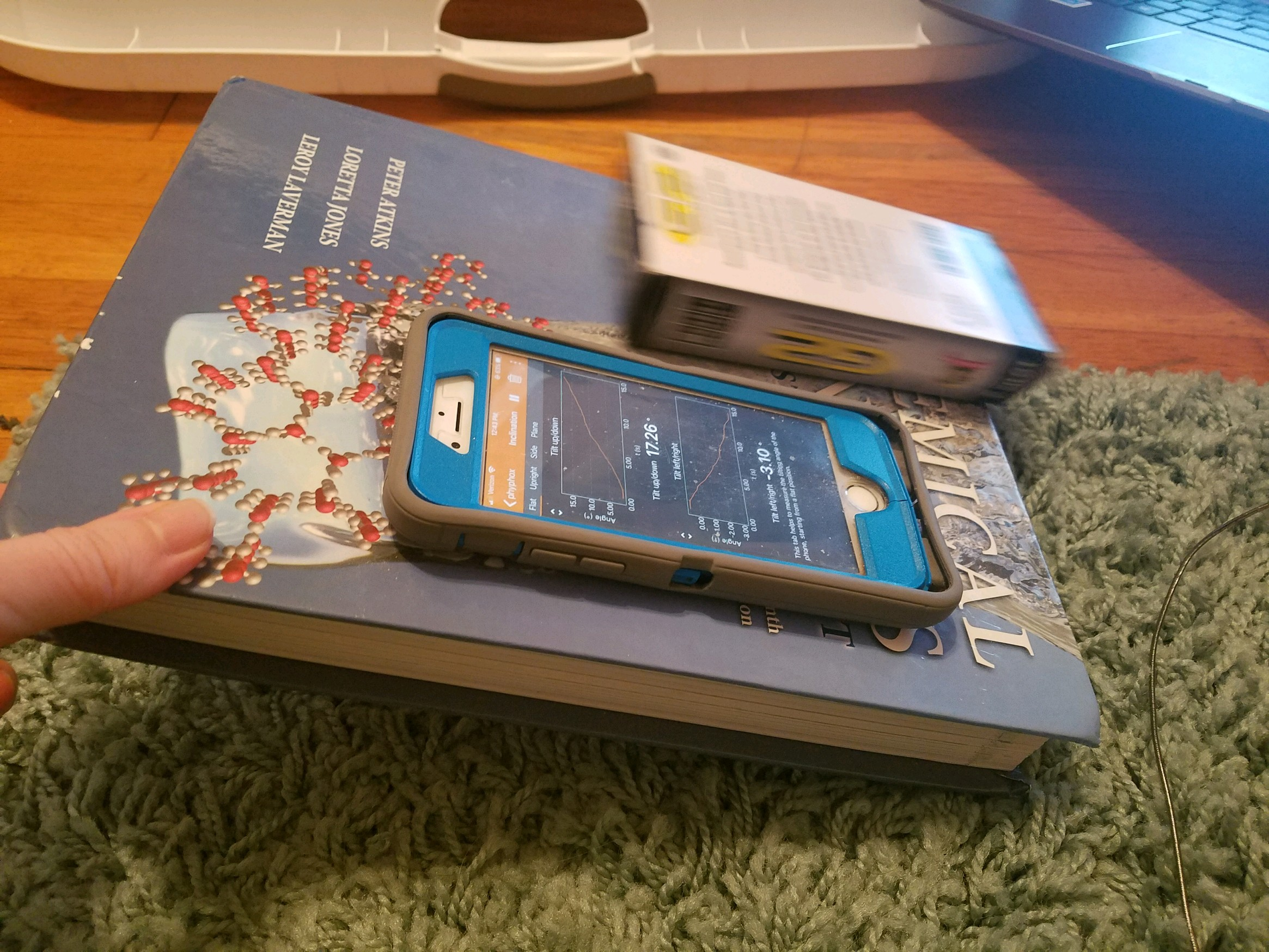 Phone and pen box on a tilted textbook.