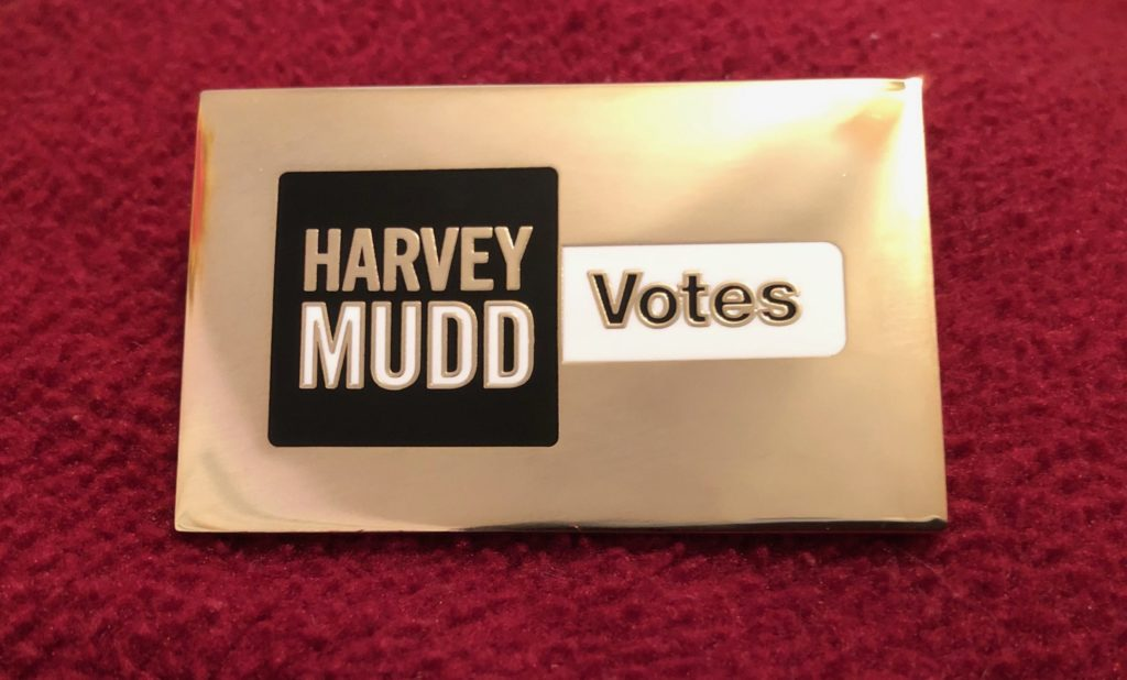 "A metal pin that reads ""Harvey Mudd Votes"""