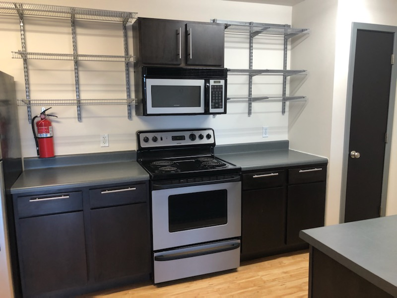 A kitchen with a stove and microwave. The counters and shelves are empty.