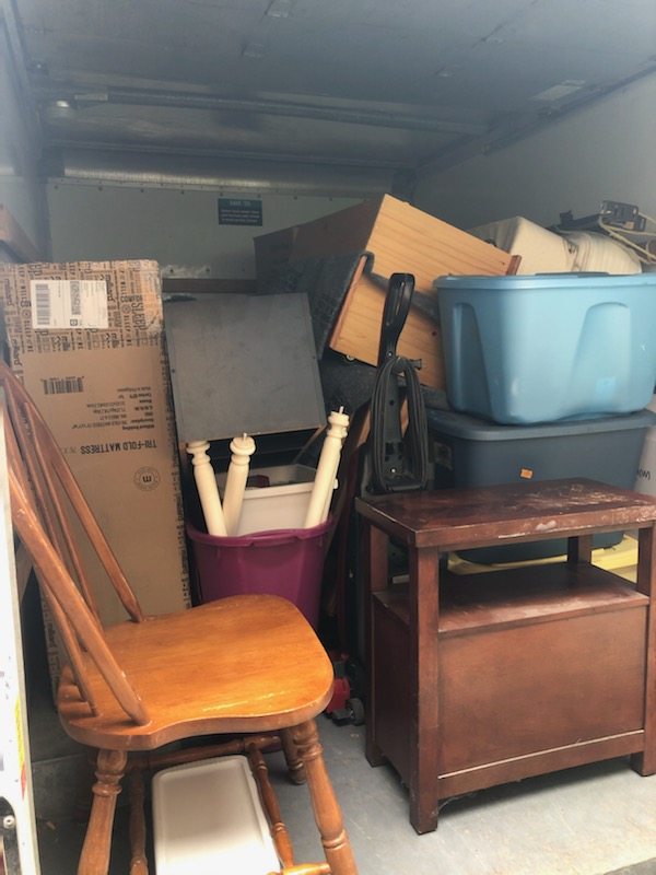 The back of a moving truck, with a chair, a bedside table, and several boxes visible.