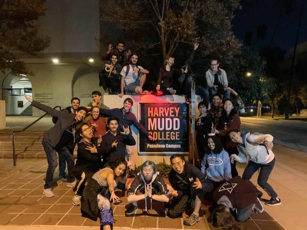 """A group of Mudd students in front of a sign that says """"Harvey Mudd College Pasadena Campus"""""""