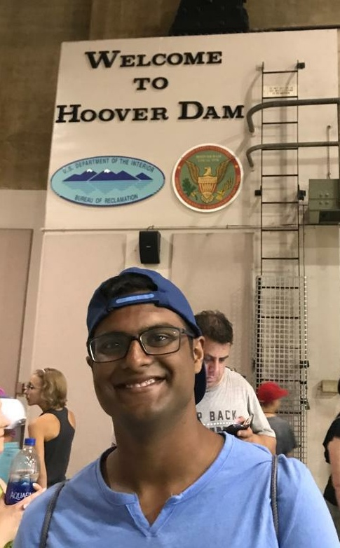"""Kausik underneath a sign reading """"Welcome to the Hoover Dam"""""""