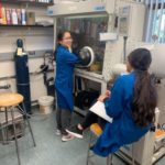 Emily and another student in lab coats next to a large piece of chemistry equipment