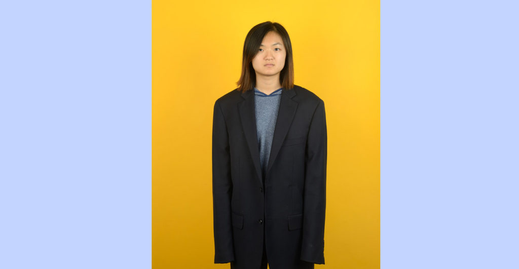 Image of girl in man's suit looking at camera to advertise 2018 Fall Semester Exhibition at Harvey Mudd College