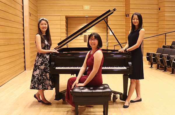 HMC seniors pose by piano: Haoxing Du, Nora Hu and Maggie Li